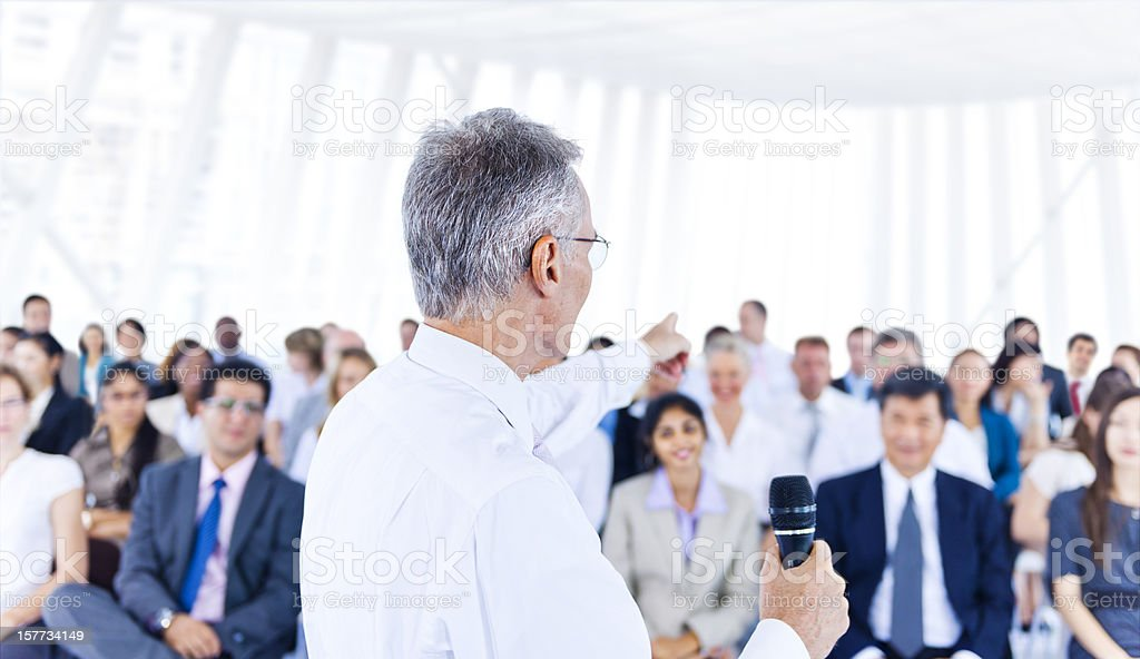 Senior man with microphone in front of audience royalty-free stock photo