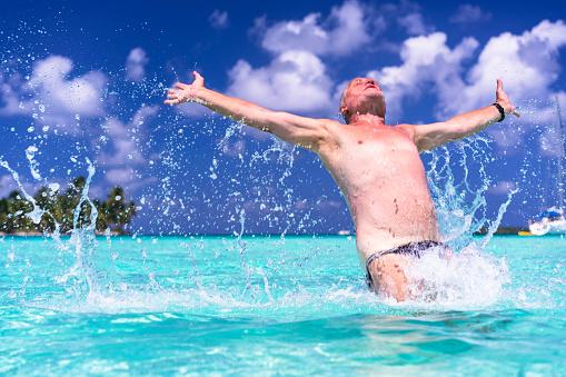 Senior man  with open arms on beach  of Isla de Perro Island in Caribbean See, Panama