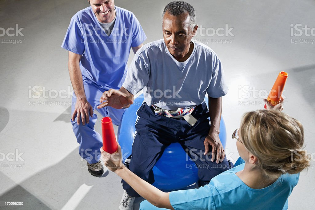 Senior man with physical therapists using stability ball and con royalty-free stock photo