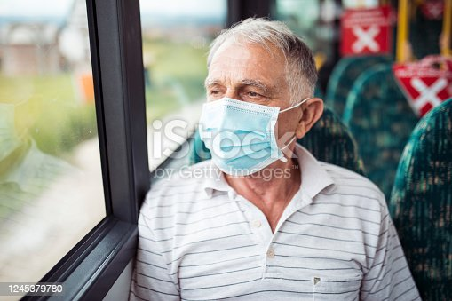 Senior man with respiratory mask traveling in the public transport by bus