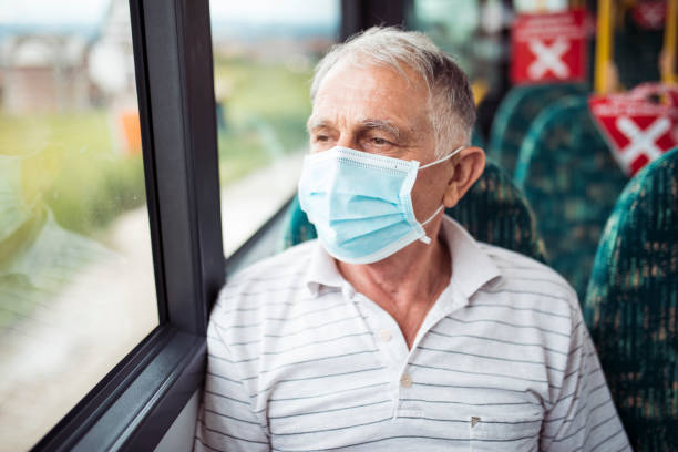 Senior man with respiratory mask traveling in the public transport by bus Senior man with respiratory mask traveling in the public transport by bus only senior men stock pictures, royalty-free photos & images