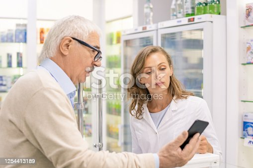 Senior man with smartphone showing name of new medicine to young female consultant in drugdstore and asking if they have it