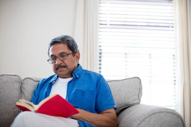 ältere mann mit brille einen roman lesen - haushaltsbuch führen stock-fotos und bilder