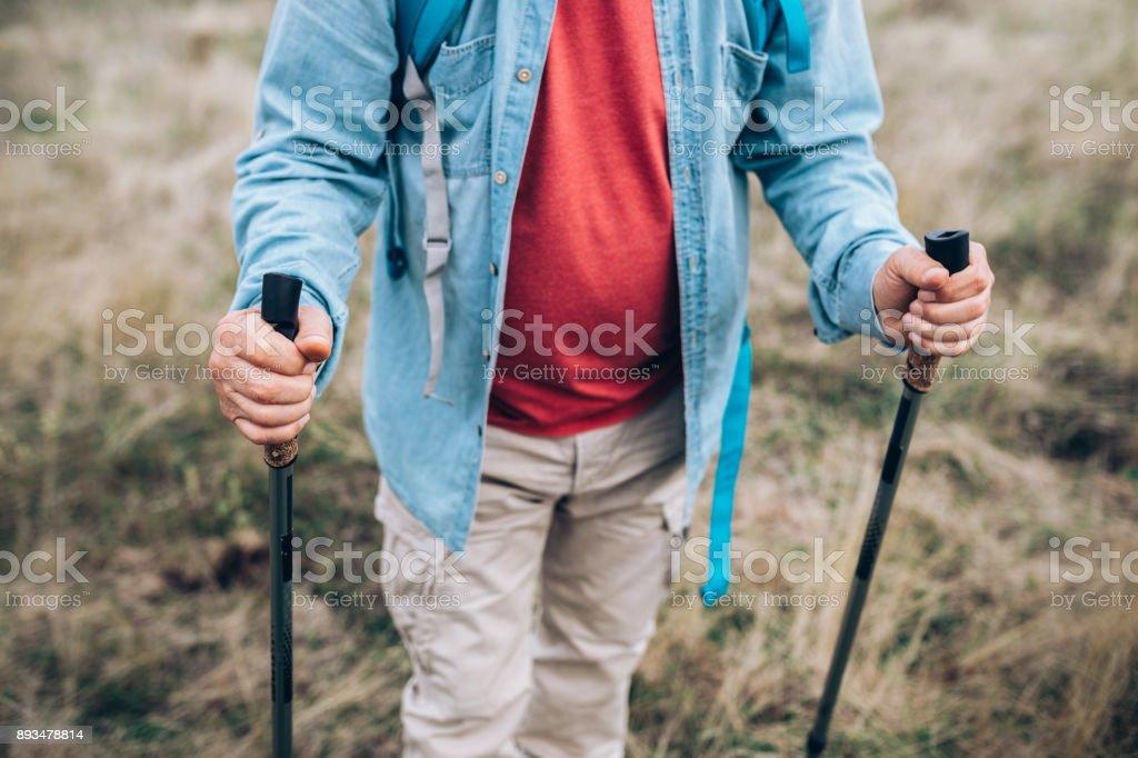 Senior man with sticks for hiking stock photo