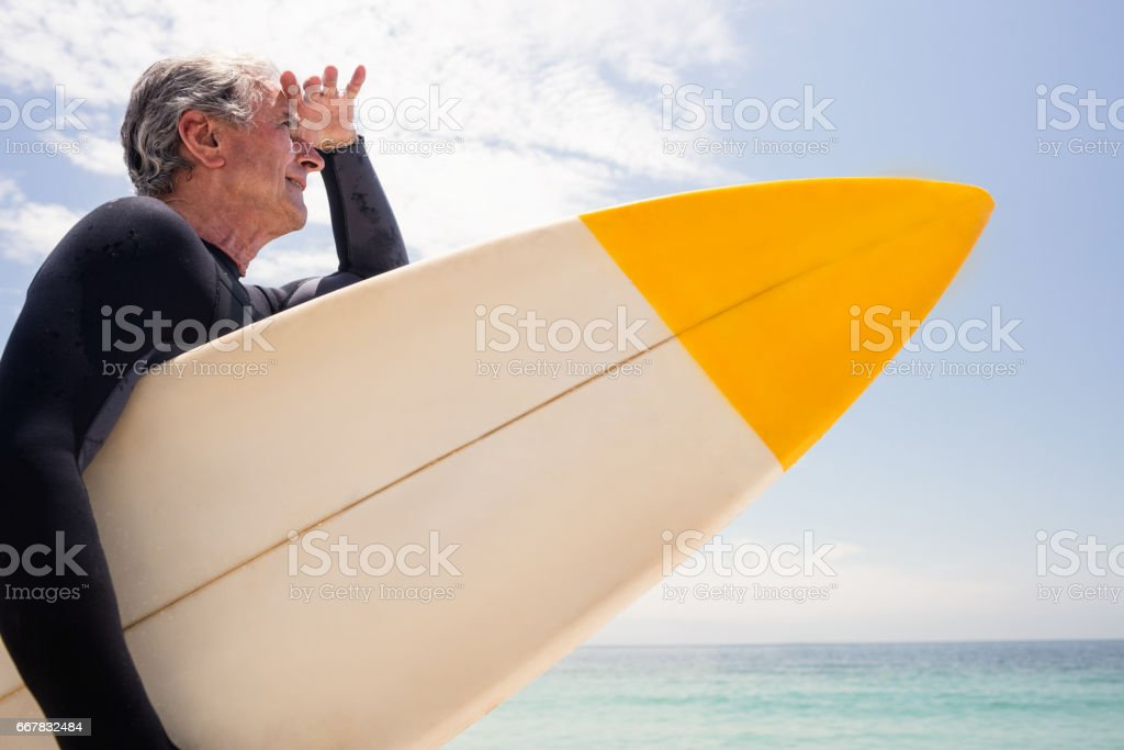 Senior man with surfboard shielding eyes at beach stock photo