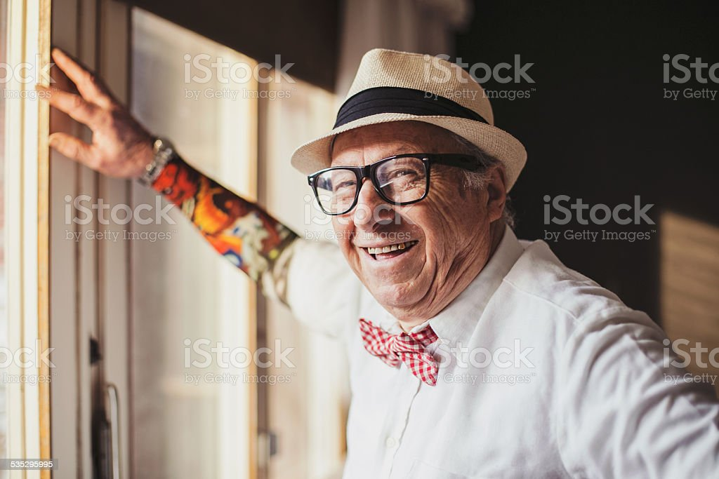 Senior man with tattoo smiling and looking at camera stock photo