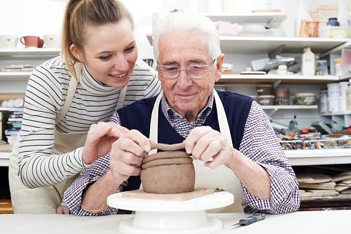 Senior Man With Teacher In Pottery Class