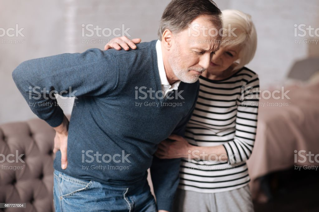 Senior man with terrible backache near wife stock photo