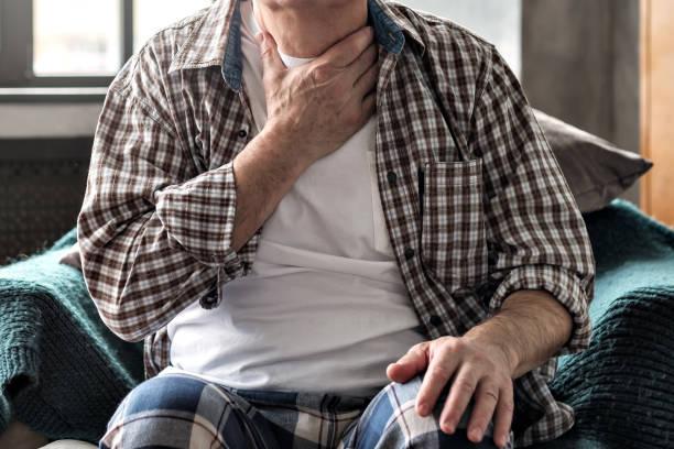 Senior man with throat pain sitting on sofa. stock photo
