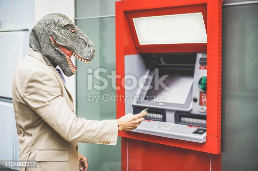 Senior man with t-rex mask withdraw money from bank cash machine with debit card - Crazy new trends advertising concept - Focus on man face