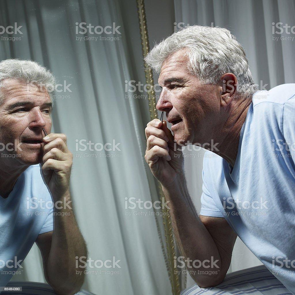 Senior man with tweezers plucking nose hair photo libre de droits