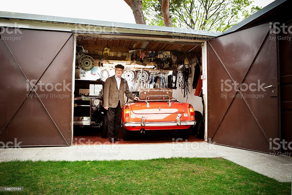 Senior man with vintage car in garage stock photo
