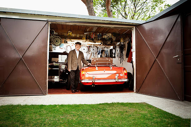 alter mann mit vintage-auto in der garage - alten muscle cars stock-fotos und bilder
