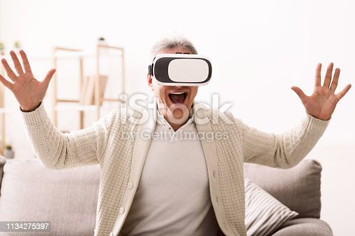 Augmented reality. Senior man with virtual headset playing videogame at home
