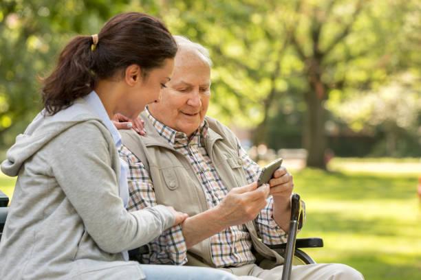 Seniorenmann mit Rollstuhl und Betreuer – Foto