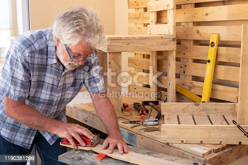 Senior man with white hair enjoying work with wooden pallet to create new objects for home. A chair is almost finished and another is in work. Free time well spent
