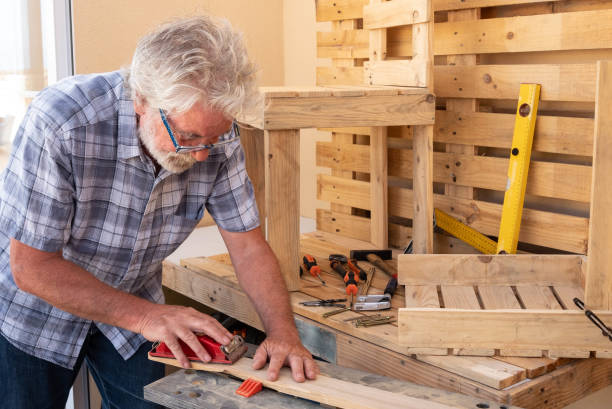 Senior man with white hair enjoying work with wooden pallet to create new objects for home. A chair is almost finished and another is in work. Free time well spent Senior man with white hair enjoying work with wooden pallet to create new objects for home. A chair is almost finished and another is in work. Free time well spent hobbies stock pictures, royalty-free photos & images