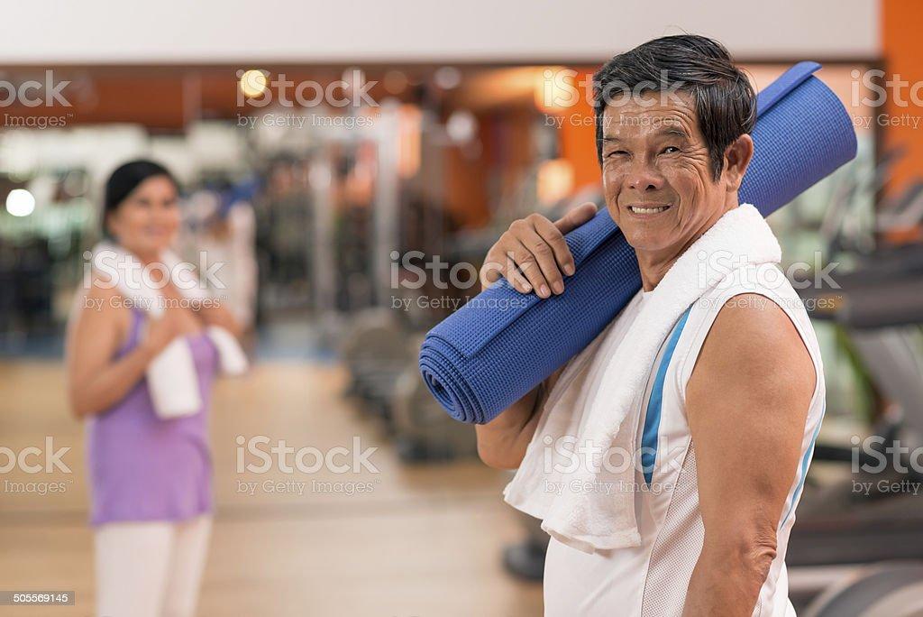 Senior man with yoga mat stock photo