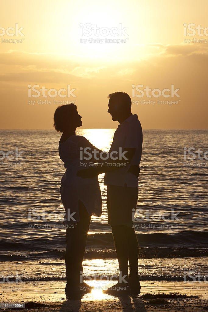 Senior Man & Woman Couple on Beach at Sunset royalty-free stock photo