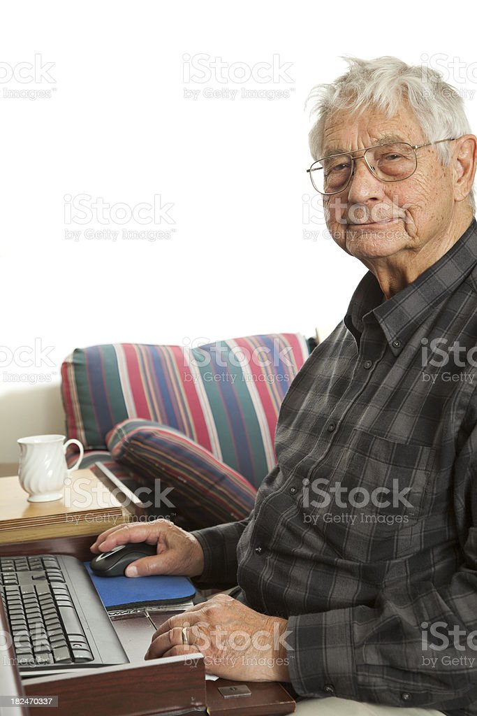 senior man working at computer desk with keyboard and mouse royalty-free stock photo