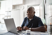 istock Senior man working at laptop at home 1219569802