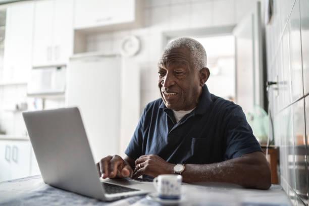 starszy mężczyzna pracujący na laptopie w domu - dojrzały zdjęcia i obrazy z banku zdjęć