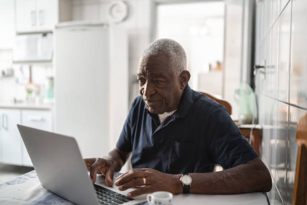 Senior man working at laptop stock photo