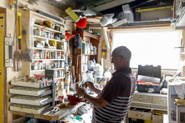 Senior Man Working In His Workshop Happily Retired Senior Man Working In His Workshop in Australia man cave stock pictures, royalty-free photos & images