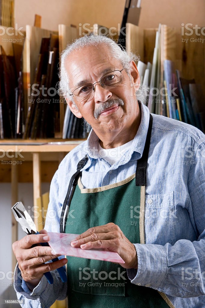 Senior man working in stained glass studio workshop stock photo