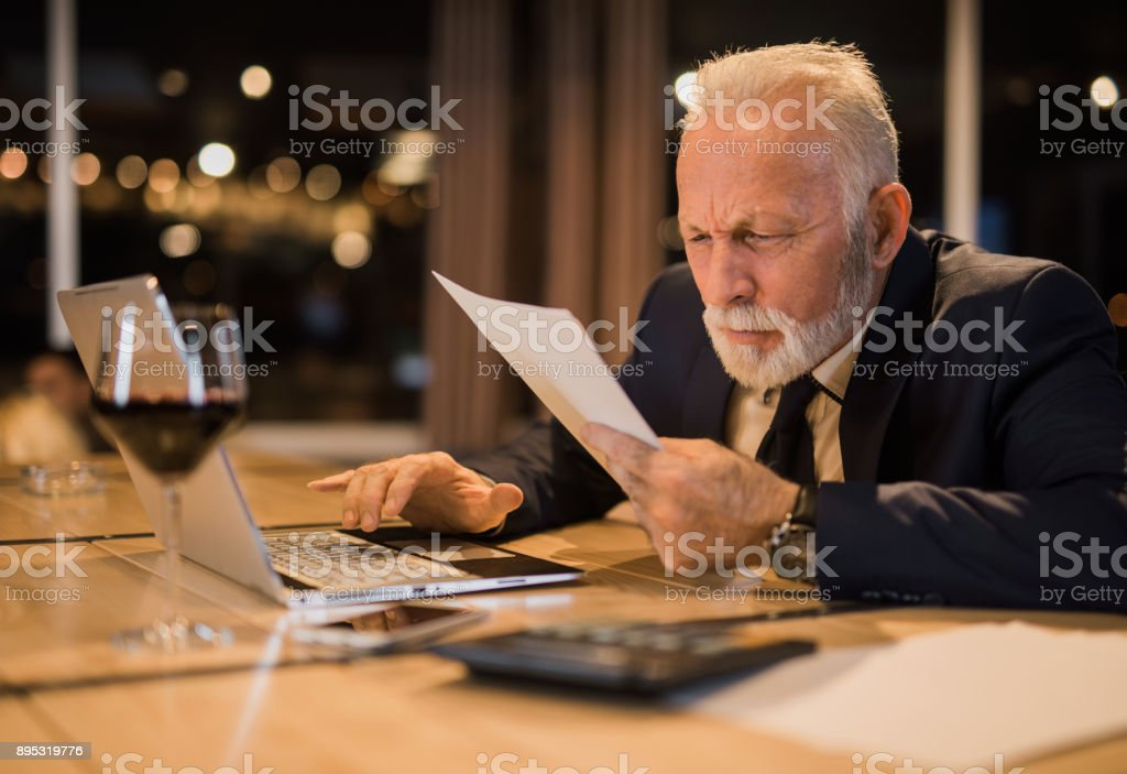 Senior man working late and struggling to read a document. stock photo