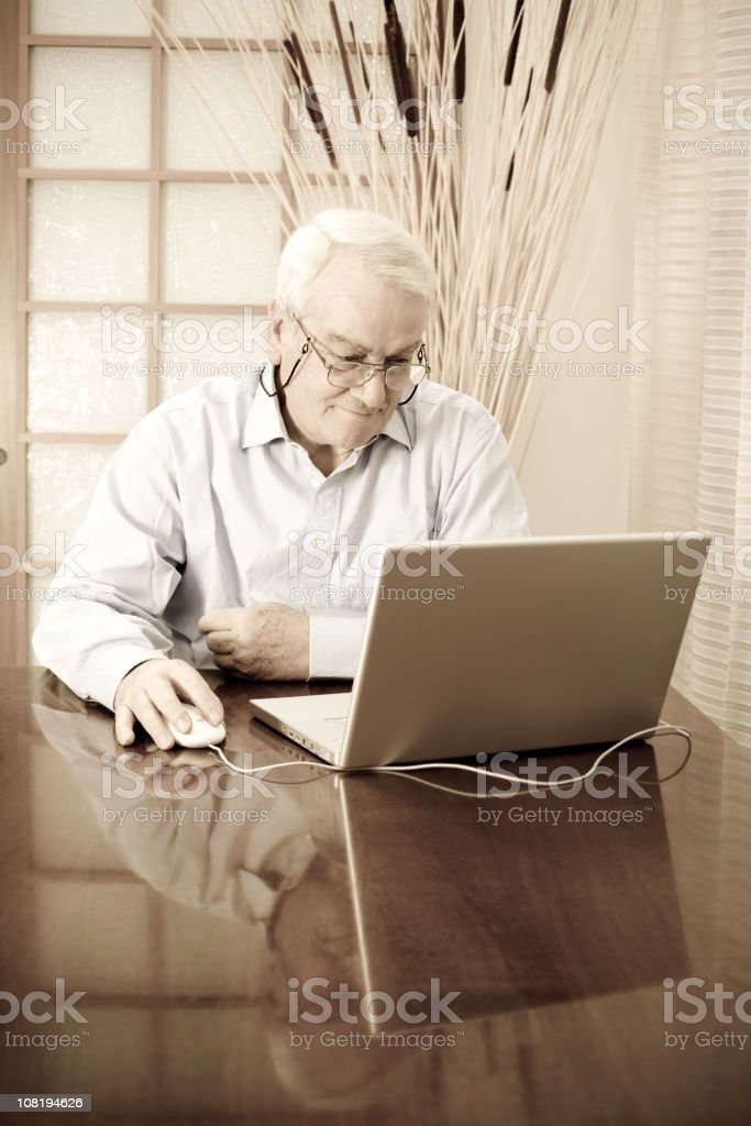 Senior man working on a laptop at home royalty-free stock photo