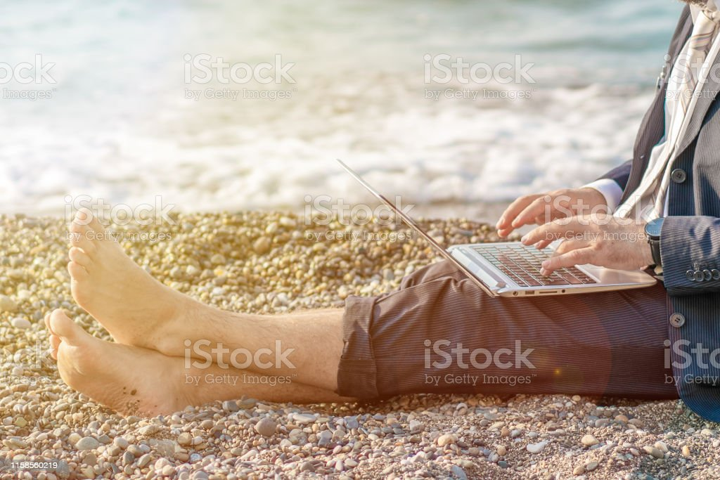 Senior man working on his laptop on the beach. Close up