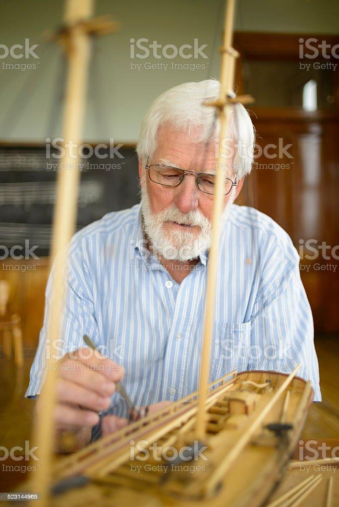 Senior Man Working on Wood Sailing Ship Model stock photo