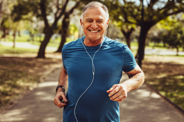 Senior man working out for good health Portrait of a senior man in fitness wear running in a park. Close up of a smiling man running while listening to music using earphones. exercising stock pictures, royalty-free photos & images