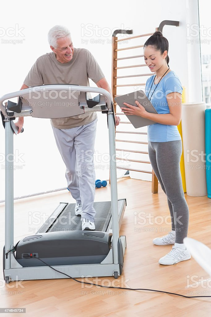 Senior man working out with his trainer stock photo