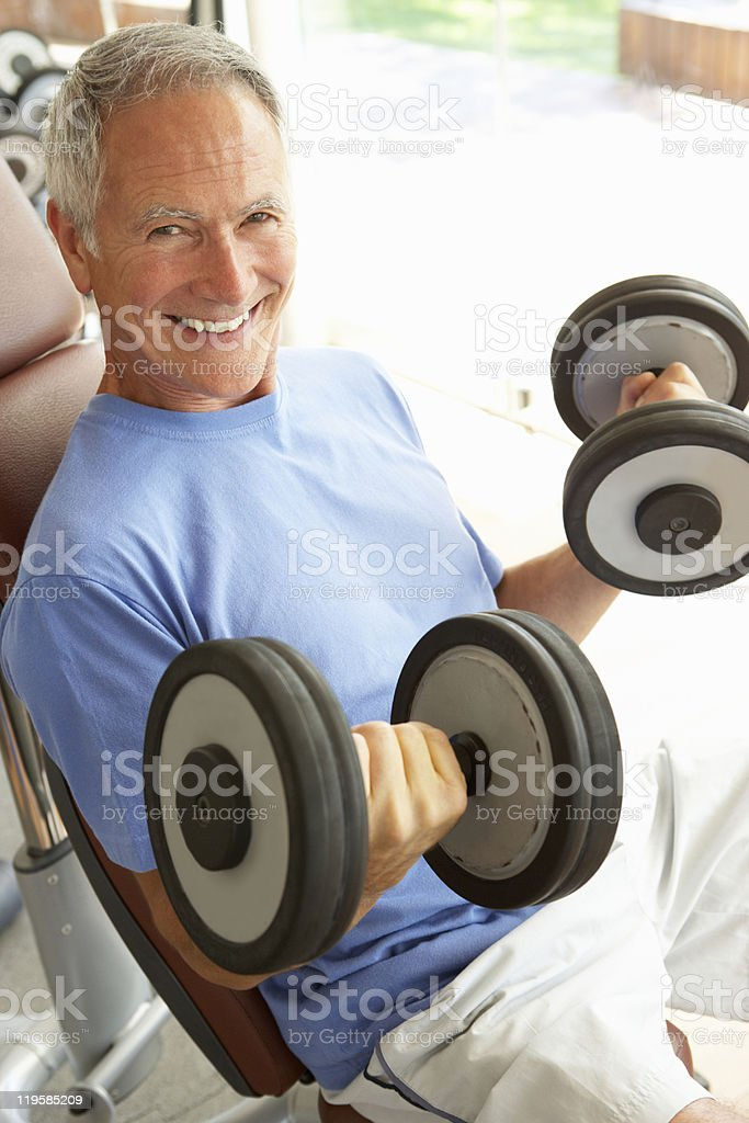 Senior man working out with weights at the gym royalty-free stock photo