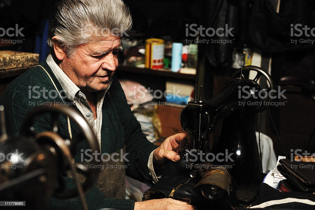 Senior man working with old machine in his own workshop royalty-free stock photo