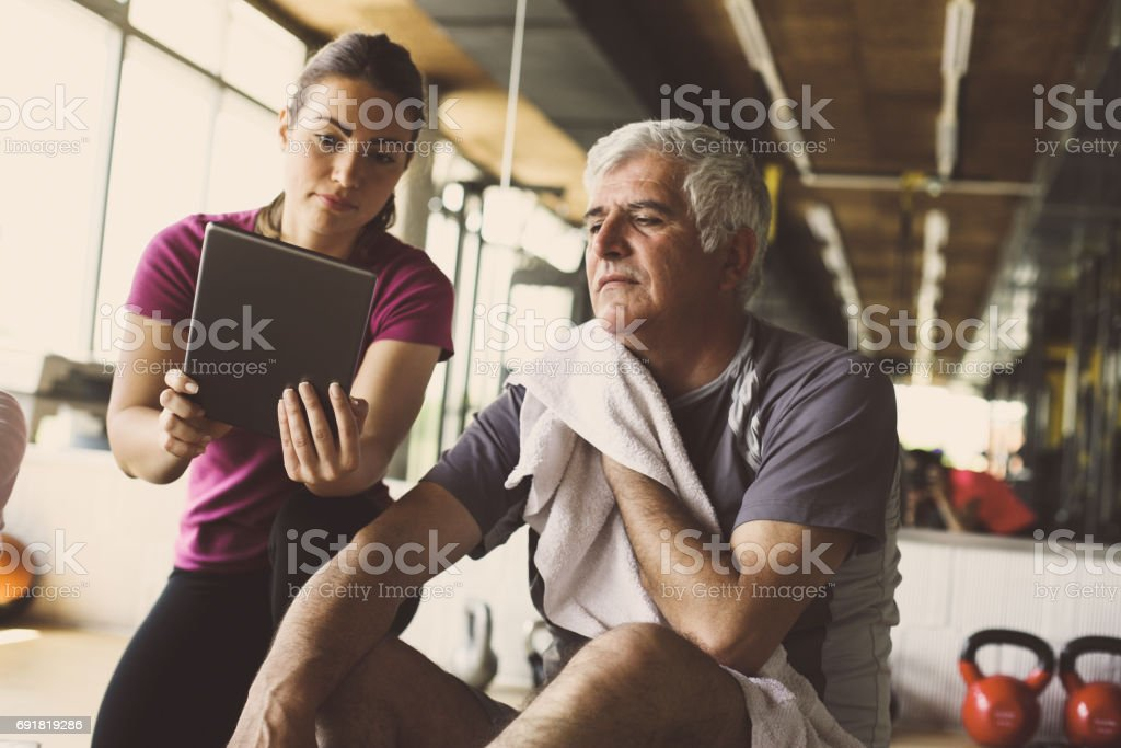 Senior man workout in rehabilitation center. Personal trainer showing something  on digital tablet. stock photo