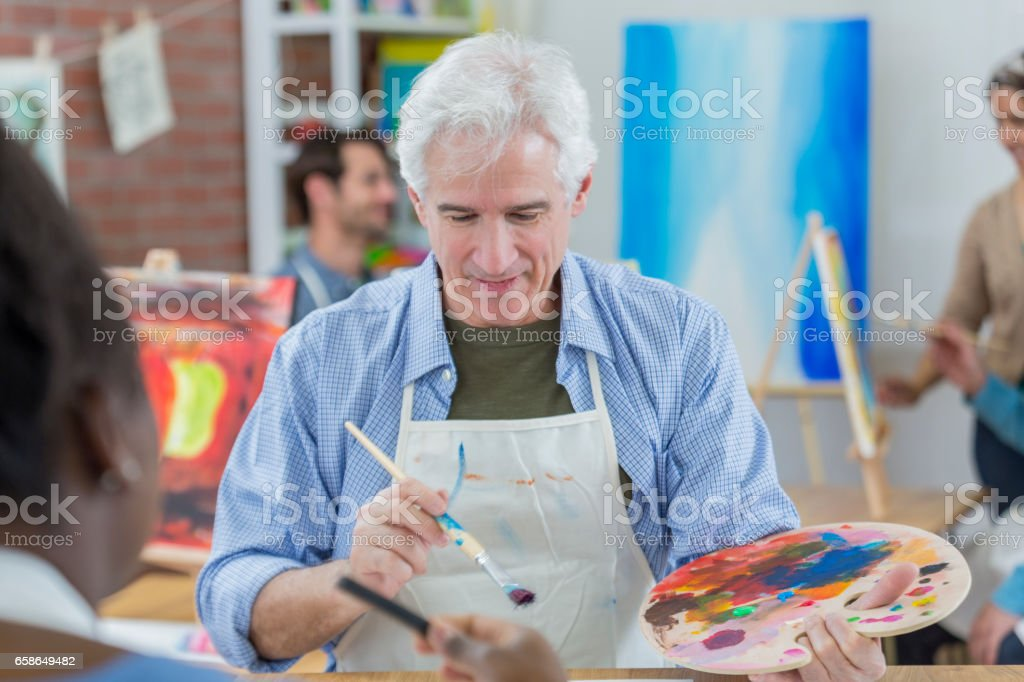 Senior man works on painting in art class stock photo
