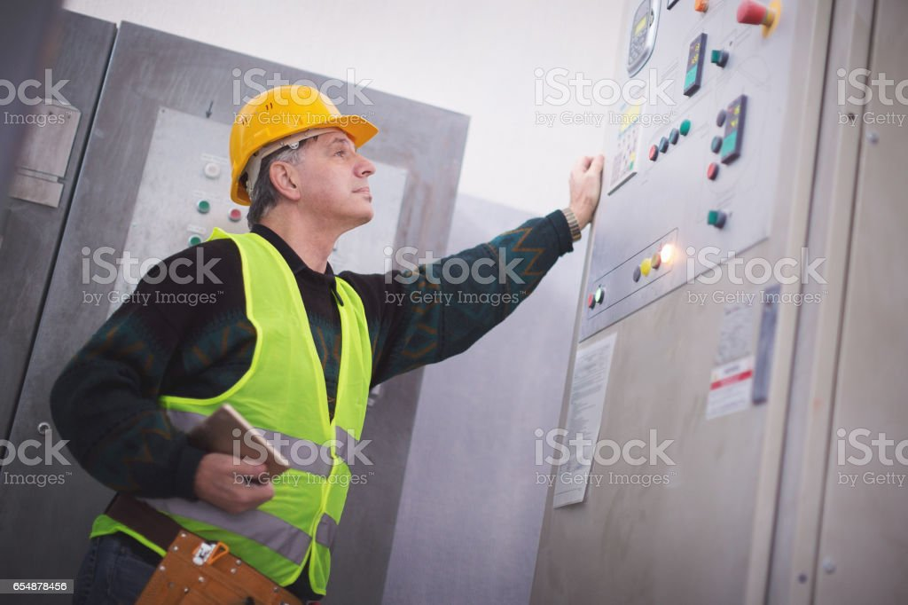 Senior manager checking machines in factory stock photo