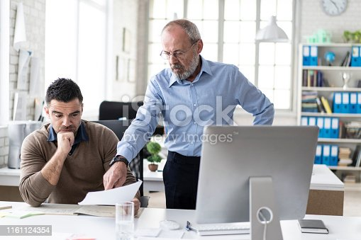 Male coworkers discussing in office, looking at documents.