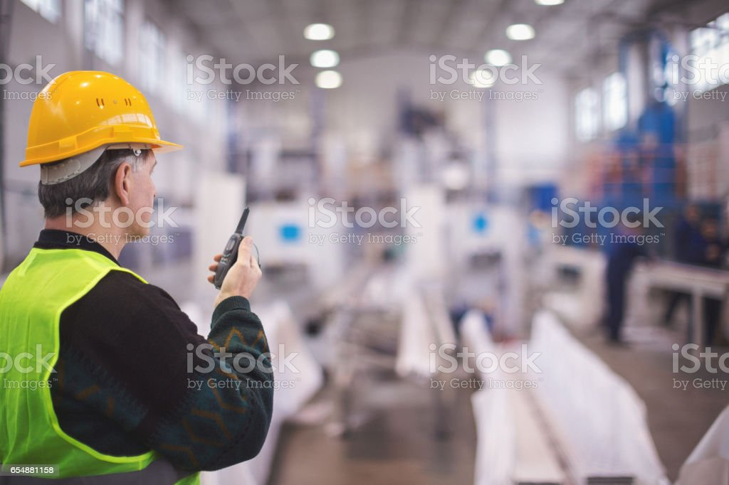 Senior manager talking on walkie talkie in factory stock photo