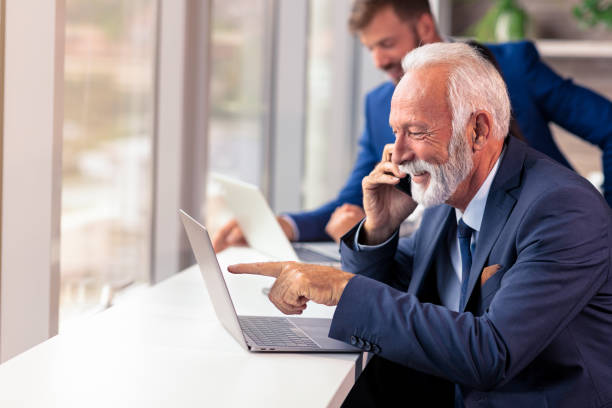 Senior manager using a mobile phone with young colegues in background stock photo