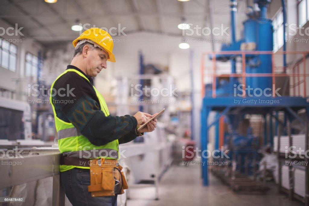 Senior manager using tablet pc in factory stock photo