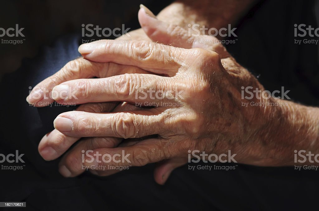 Senior man's arthritic hands in shadow. stock photo
