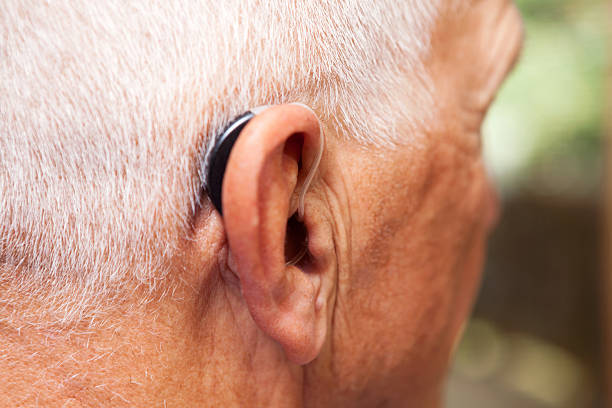 senior man's ear with hearing aid - hearing loss stock pictures, royalty-free photos & images