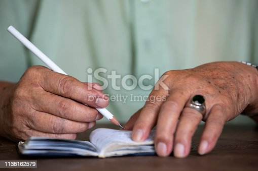 Senior man's hand writing letter on white notebook, Wooden background, A white pencil, Close up & Macro shot, Selective focus, Stationery concept