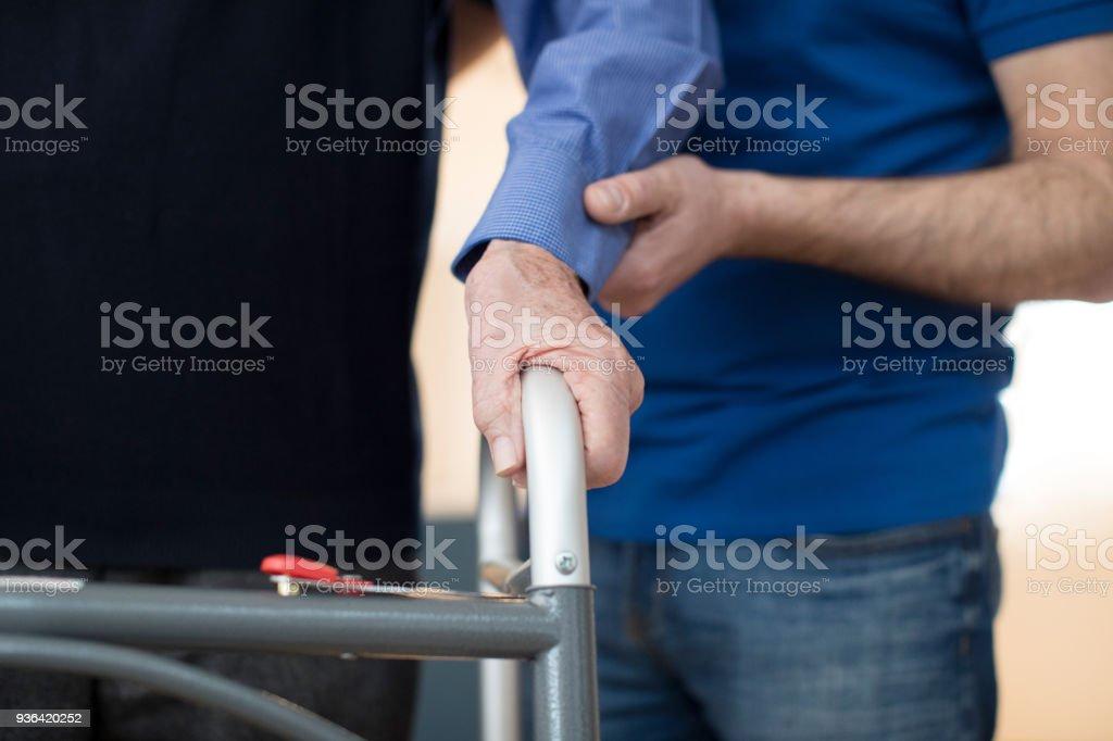 Senior Mannhände auf Rahmen mit Pflegedienst im Hintergrund laufen – Foto