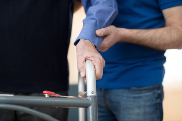 senior man's hands on walking frame with care worker in background - fragility stock pictures, royalty-free photos & images