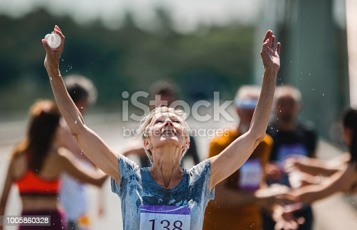 Senior woman running a marathon on the road and refreshing herself with water from a cup. There are people in the background.